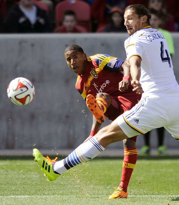 Real Salt Lake forward Joao Plata (8) kicks the ball around the defense of Los Angeles Galaxy defender Omar Gonzalez (4) during a game at Rio Tinto Stadium on Saturday, March 22, 2014.