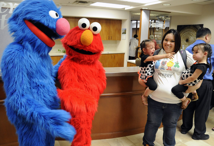 "Elmo and Grover of Sesame Street Live frighten 2-year-old Gabriella Barbone, left, while being held by her mother, Andrea, center, along with her sister Avery, right, at the Tri-Cities Cancer Center Tuesday afternoon. The Sesame Streets Friends will be performing their ""Make A New Friend"" production on Wednesday at the Toyota Center."