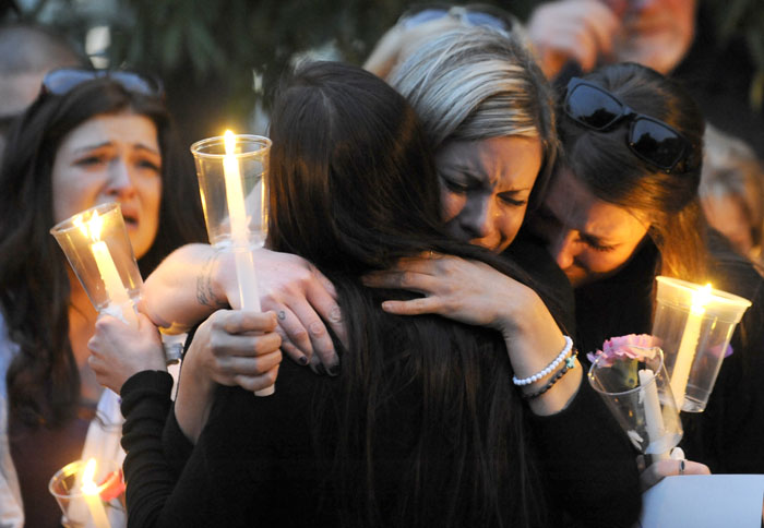 Carisa Meeker, center, and Brittany Stearns hug Jamie Roberts after Roberts talked about the type of person Monique Williams was during a candlelight vigil held at the John Dam Plaza in Richland on Friday, May 23, 2014. Williams (29) was killed in her home by her ex-boyfriend Aaron Newport on Monday in what officials are calling a murder-suicide.