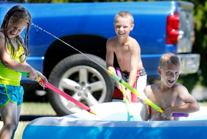 Gavin Smith, 10, sprays his sister Madelyn (7) in the face as their brother Payton, 11, loads up his water gun in the pool while playing in the heat on Monday afternoon in front of their home in Kennewick. Today's forecast is for sunny skies with highs in the 100s.