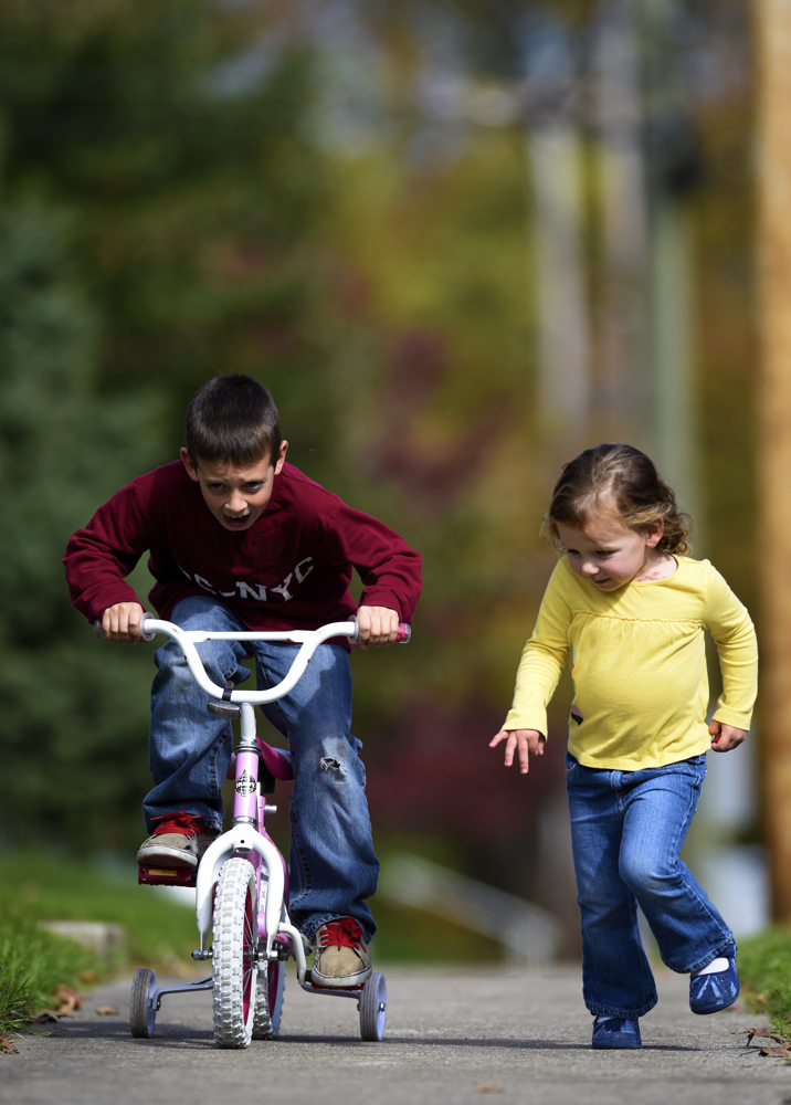 Gregg Carney (9) races his sister Siddalee (3) on the sidewalk outside their home in the early afternoon.