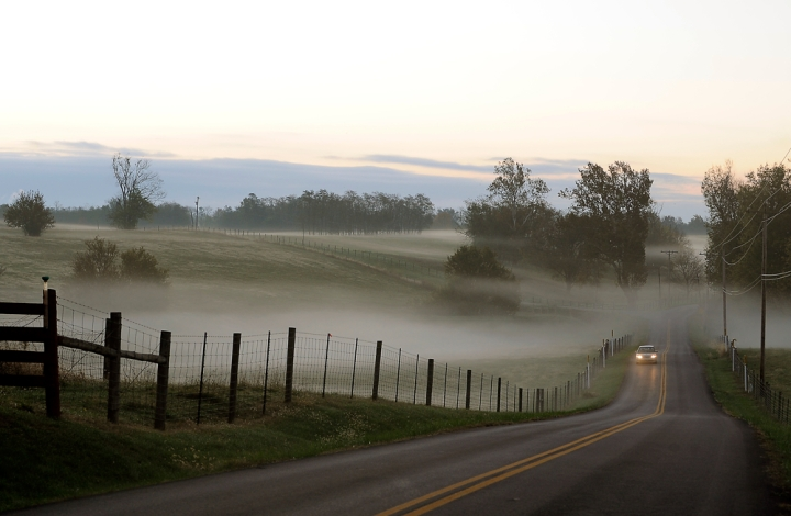 A car approaches through the morning fog on Walnut Meadow Road west of Berea.