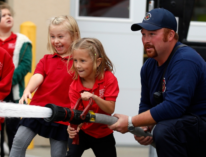Harbor Blindauer, left, enjoys watching as Sawyer Grimsley gets help from Zach Dalrympk, a paramedic/firefighter with the Mitchell Fire Department, using the fire hose as first graders from John Paul II Elementary School visited the Mitchell Fire Department on Monday afternoon as part of fire prevention week. (Matt Gade/Republic)