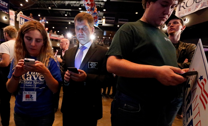 Crowd members, including state senate majority leader Tim Rave, check their phones during the Republican Election Party on Tuesday night at The District restaurant in Sioux Falls. (Matt Gade/Republic)