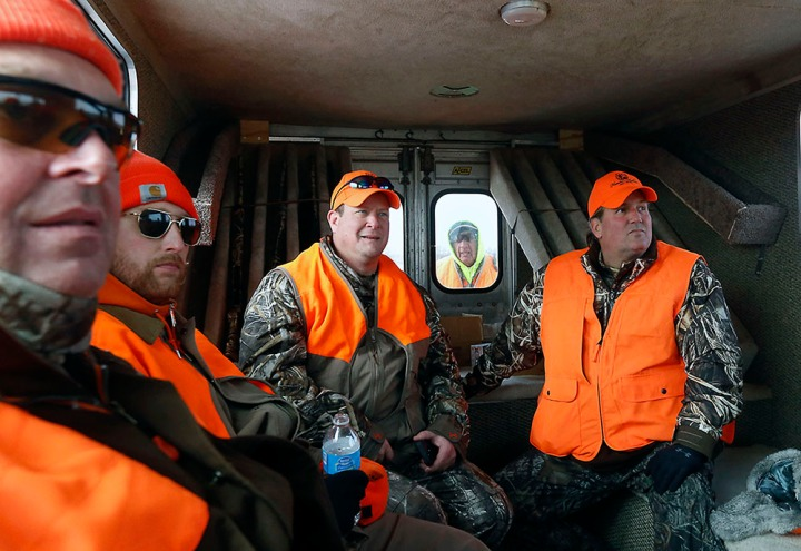 From left; Dan Holbrook, Jesse Henderson, Jeff Temple and John Ferszt ride inside the truck to the next location as Dave Vireck rides outside the back of the truck during a hunting trip at Firesteel Creek Hunting Lodge off HWY 281 on Tuesday morning near Plankinton. (Matt Gade/Republic)