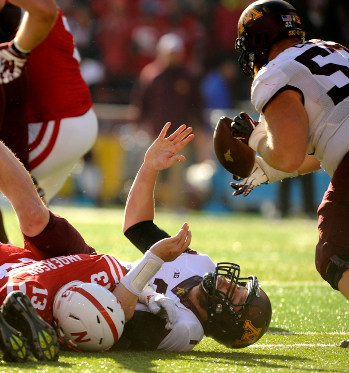 Minnesota Golden Gophers quarterback Mitch Leidner (7) fumbles the ball right into the hands of Minnesota Golden Gophers offensive lineman Zac Epping (52) as he was tackled by Nebraska Cornhuskers linebacker Zaire Anderson (13) during a game on Saturday at Memorial Stadium in Lincoln. (© Matt Gade)