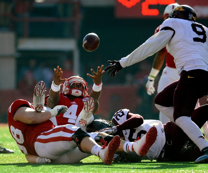 Nebraska Cornhuskers quarterback Tommy Armstrong Jr. (4) reaches out for the ball as he lost while being tackled by Minnesota Golden Gophers defensive back Jalen Myrick (28) during a game on Saturday at Memorial Stadium in Lincoln. Armstrong was ruled down on the play before losing control of the ball. (© Matt Gade)