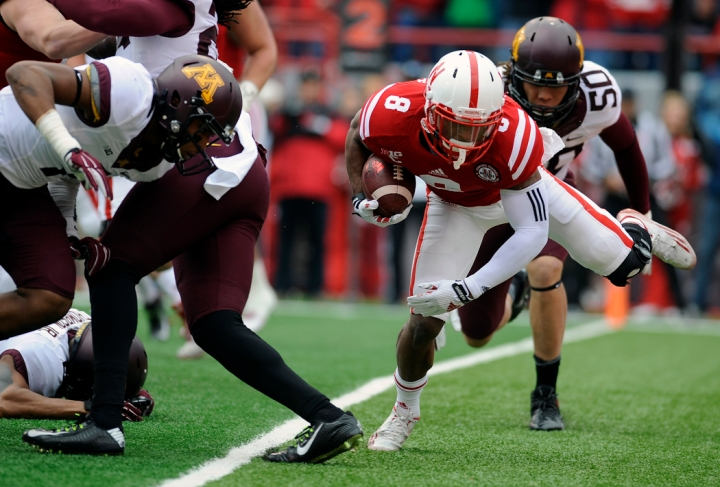 Nebraska Cornhuskers running back Ameer Abdullah (8) scores a touchdown stumbling into the endzone through the Minnesota Golden Gophers defense during a game on Saturday, Nov. 22 in Lincoln, Neb. (© Matt Gade)