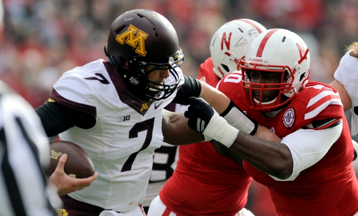 Nebraska Cornhuskers defensive end Greg McMullen (90) grabs Minnesota Golden Gophers quarterback Mitch Leidner (7) for tackle for loss during a game on Saturday at Memorial Stadium in Lincoln. (© Matt Gade)