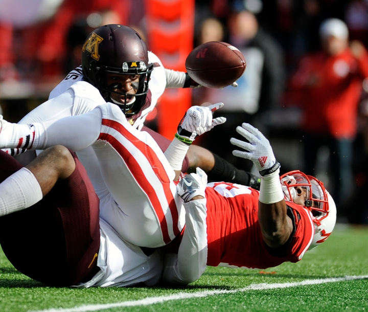 Nebraska Cornhuskers wide receiver De'Mornay Pierson-El (15) loses control of the ball out at the goal line as he was tackled by Minnesota Golden Gophers defensive back Damarius Travis (7) and Minnesota Golden Gophers defensive back Jalen Myrick (28) during a game on Saturday at Memorial Stadium in Lincoln. El was ruled to have crossed the goal line with the ball and the touchdown negated the fumble. (© Matt Gade)