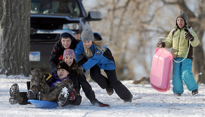 Mckenzie Endorf (13) and Alex Kuck (13) get a push from Grace (12) and Tristan Endorf (13) down the hill as 10-year-old Anna Endorf looks on while sledding on a hill next to Lake Mitchell on Friday afternoon in Mitchell. (Matt Gade/Republic)