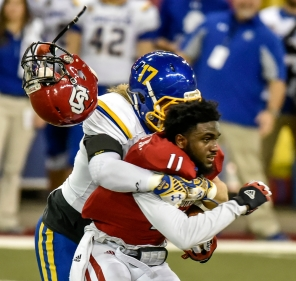South Dakota State linebacker Patrick Schuster (17) knocks the helmet off University of South Dakota Coyotes wide receiver Eric Shufford (11) during a game between the University of South Dakota Coyotes and the South Dakota State Jackrabbits on Saturday at the DakotaDome in Vermillion. (Matt Gade/Republic)