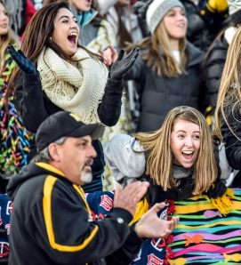 The Mitchell student section including Gracie Kattner, right, and Paige Grace, top left, cheer on the Kernels during a game in the first round of the class 11AA playoffs on Thursday night at Joe Quintal Field in Mitchell. (Matt Gade/Republic)
