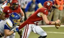 South Dakota State defensive lineman Cole Langer (54) brings down University of South Dakota Coyotes quarterback Ryan Saeger (2) during a game between the University of South Dakota Coyotes and the South Dakota State Jackrabbits on Saturday at the DakotaDome in Vermillion. (Matt Gade/Republic)