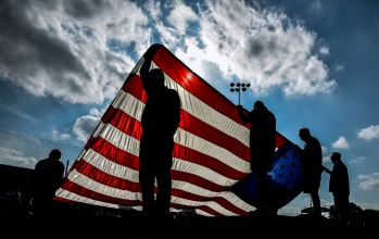 Members of the Mitchell Exchange Club hold up the flag of the United States of America for the national anthem prior to the start of the Lennox Millbank game which was the first game of the 2015 South Dakota State Amatuer Tournament on Wednesday at Cadwell Park. (Matt Gade/Republic)