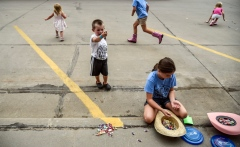 Grace Robb (10), front, counts her money as Thomas (4) shows off shows his parents the piece of candy he got while Eve (2), back left, and Nora (8), back center, race out for more candy as the Scottie Stampede Parade rolls down Main street on Saturday in Scotland. (Matt Gade/Republic)