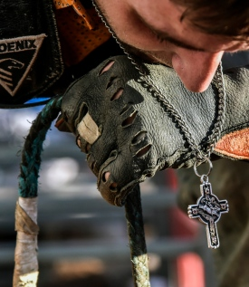 Dusty May's cross dangles as the Springfield resident gets set to a ride a bull during the Miller Lite Bull Bash on Wednesday night at Horseman's Sports Arena in Mitchell. (Matt Gade/Republic)