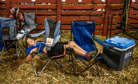 Seven-year-old Maddie Lehrkamp, of Highmore, takes a break resting on a pair of fold up chairs inside the beef complex during the first day of the South Dakota State Fair on Thursday in Huron. (Matt Gade/Republic)