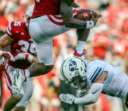 Nebraska Cornhuskers quarterback Tommy Armstrong Jr. (4)leaps over a BYU defender during a game on Saturday afternoon in Lincoln, Nebr.. (Matt Gade/Republic)