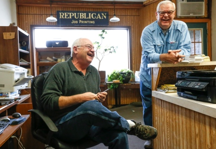 Craig, at left, and Duke Wenzel share a laugh, while Craig works on advertisements and Duke prepares to shoot his last photos of school kids at Wessington Springs Elementary School. (Matt Gade/Republic)
