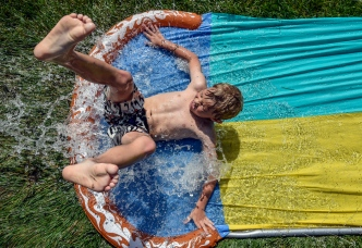 Canon Moller (8) goes down the slip n slide while hanging out at the Widstrom's on Wednesday afternoon. Today's forecast calls for a slight chance of showers and thunderstorms after 1pm. Mostly cloudy, with a high near 80. Chance of precipitation is 20%. (Matt Gade/Republic)