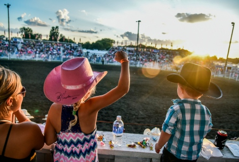 Eight-year-old Jaycee pumps her fist while watching the bareback riding competition with mom Caitlyn Lachnit, left, and brother Tayton (2), all of Alexandria, on Thursday night during the first night of the 45th annual Corn Palace Stampede Rodeo at Horseman Arena in Mitchell.(Matt Gade/Republic)
