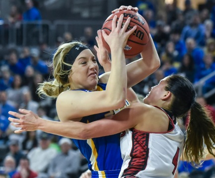 South Dakota State University's Madison Guebert (11) gets tangled up with the University of South Dakota's Tia Hemiller (4) going to the basket during a game in the Summit League conference championship on Tuesday at the Denny Sanford Premier Center in Sioux Falls. (Matt Gade/Republic)