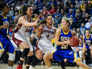 South Dakota State University's Chloe Cornemann (22) looks for an outlet after making a rebound in front of University of South Dakota's Kate Liveringhouse (34) and University of South Dakota's Tia Hemiller (4) during a game in the Summit League conference championship on Tuesday at the Denny Sanford Premier Center in Sioux Falls. (Matt Gade/Republic)