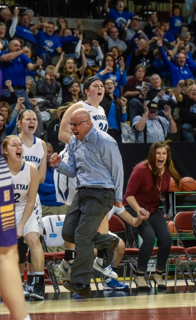Dakota Wesleyan Head Coach Jason Christensen and the Tigers bench celebrate a Dakota Wesleyan's Erica Herrold (14) basket with the foul call late during the first round of the NAIA Division II women's national tournament against Haskell Indian Nation University on Wednesday morning at the Tyson Events Center in Sioux City, Iowa. (Matt Gade/Republic)