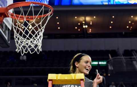 South Dakota State University's Kerri Young (10) poses with a piece of the net after taking part in the traditional cutting down of the net following the Jackrabbits win over the University of South Dakota Coyotes in the Summit League conference championship on Tuesday at the Denny Sanford Premier Center in Sioux Falls. (Matt Gade/Republic)