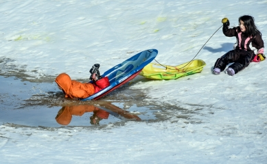 Mateo Hotchkiss, 3, dives into a puddle of water on his sled in front of his sister Ana, 6, while sledding down the amphitheater hill at Lake Mitchell on Sunday in Mitchell. (Matt Gade/Republic)