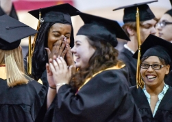Lizdiany Andujar, left, shares a laugh with Dakota Anderson, right, and Rachel Bechen, center, while waiting to walk for the processional Mitchell High School's commencement exercises on Sunday, May 22 at the Corn Palace in Mitchell.