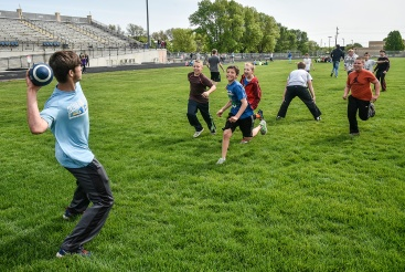 Brandon Krogman, a Mitchell High School senior, fires a pass while getting a pass rush from left Hayden Morgan, Tanner Puetz, Gavyn Erickson and Corbin Hill while playing a game of touch football between the high school kids and Gertie Belle Rogers fifth-graders at Joe Quintal Field on Monday morning. Forty-six high school students have been writing to and trading letters with two classes of fifth graders at GBR this year and Monday was the first day for them to get a chance to meet face-to-face. The high school kids gave the elementary students tours of the high school, played out on Joe Quintal Field for games and finished with pizza for lunch before the fifth-graders walk back to GBR. (Matt Gade/Republic)