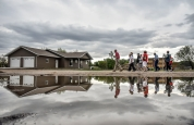 About a dozen people take a walk down S. Seaman street seeing the damage of where the tornado came through as part of the one year anniversary activities on Tuesday, May 10 in Delmont.