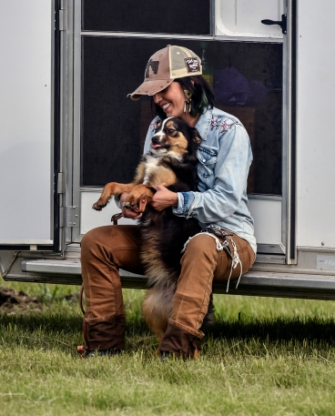 Rudie Hepper, of Mobridge, plays with a dog who wandered over for some attention while waiting to compete in the barrel racing later in the evening at the Wessington Springs Foothills Rodeo on Saturday, May 28 at the Jerauld County 4-H arena.