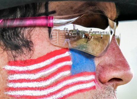 Wade Leusink, of Maurice Iowa, is seen in the reflection of the rodeo clown competing in the bull riding competition on the Saturday, June 4 in Crooks.