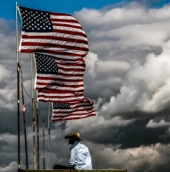 A bull rider watches the action in the steer wrestling competition from across the arena as storm clouds pass overhead during the Crooks Rodeo on Saturday, June 4 in Crooks.