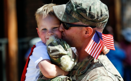Specialist Eric Simonton kisses his three-year-old son Ethan prior to the welcome home ceremony for the 155th Engineer Company on Saturday, July 2 at the Rushmore Plaza Civic Center in Rapid City. Members of the 155th spent the past 11 months on a mission in Kuwait.