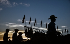 Cowboys watch the action as the sunsets on the final night of the Corn Palace Stampede Rodeo on Sunday, July 17 at Horseman's Sports Arena in Mitchell.