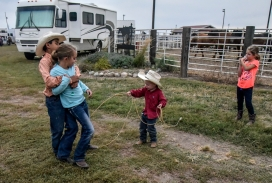 Three-year-old Rankyn Wilson gets help from Gus Wilson (11) as he holds Shaylee Porch (8) to lasso her leg while Haylee Porch (6), right, watches while playing behind the arena during the Wagner Labor Day Rodeo on Sunday in Wagner. (Matt Gade/Republic)