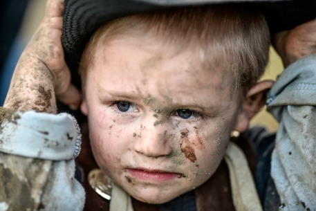Three-year-old Camdyn Fink of Woonsocket has mud covered all over his face after riding a sheep in the mutton bustin' as part of the Wessington Springs Foothills Rodeo on Saturday, May 28 at the Jerauld County 4-H arena. (Matt Gade/Republic)