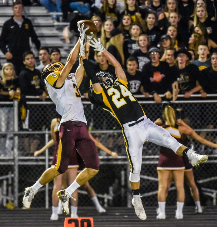 Harrisburg's Justis Clayton (3) makes a reception over Mitchell's Jed Schmidt (24) during a game on Saturday night at Joe Quintal Field in Mitchell.