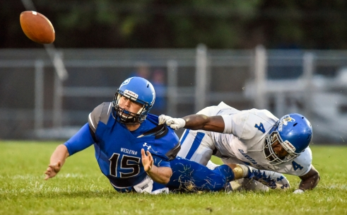 Dakota Wesleyan's Dillon Turner (15) loses the ball after being tackled by Dakota State's Darion Office (4) during a game on Friday night at Joe Quintal Field in Mitchell.
