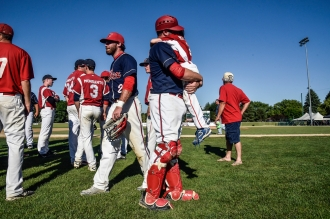 The Alexandria Angels' Chris Marek hugs his son, and the team's bat boy, Rhett Marek after defeating the Garretson Blue Jays 7-1 in the Class B state amateur championship game on Sunday at Cadwell Park in Mitchell.