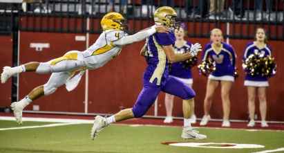 Groton's Bennett Shabazz (4) leaps onto the shoulders of Winner's Cameron Kuil (21) after a reception to try and bring him down, but Kuil would score a touchdown on the play during the Class 11B state championship game on Friday at the DakotaDome in Vermillion. (Matt Gade/Republic)