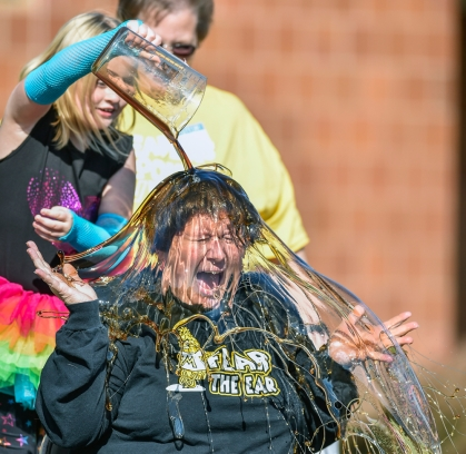 Third-grader Payton Musick pours maple syrup onto Mrs. Kim Bruguier as one of the winners of L.B. Williams annual raffle ticket sales on Friday afternoon outside of the school. Students at L.B. Williams are using the money they raised from raffle tickets to help replace outdated playground equipment.