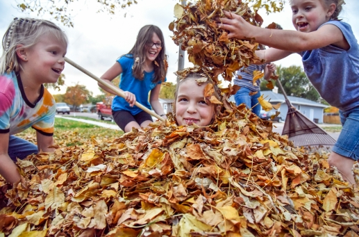 Trudie Hofer (8), right, and her sister Elsie (6), left, dump leaves on to their sister Lindy (10) while Katie Ahlers (10), second from left and Audrey Hofer (12) rake leaves for their pile to play in earlier this week. (Matt Gade/Republic)