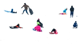 Adults and kids take advantage of snow day to go sledding at the amphitheater near Lake Mitchell on Wednesday afternoon.