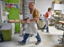 Ed Radack, left, carries out a tray of donuts while Liza Plihal works on a tray of rolls on Wednesday morning. Liza is the Radack's only full time employee besides themselves. Liza has been working with them for two years now.