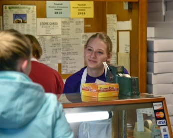 Sierra Messman helps a customer on Friday morning. Sierra is one of six high school students who work mornings before school and on Saturday mornings at the Tyndall Bakery.